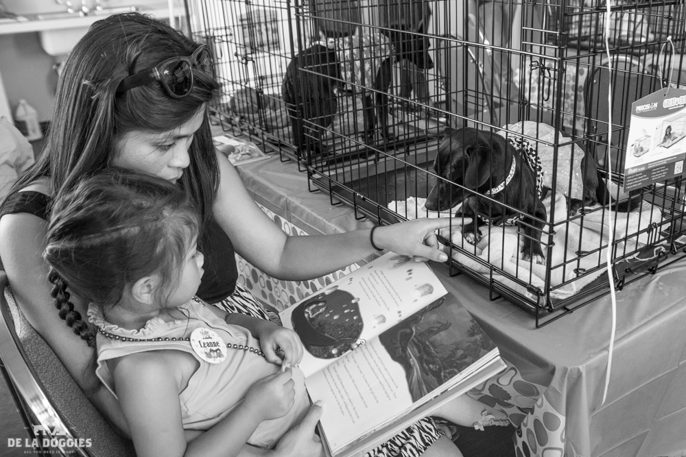 Young girl and her mom reading to dogs at South LA Animal Services as part of our Walk the Dog Collection